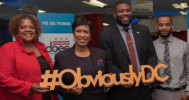 Mayor Bowser and others hold Obviously DC sign