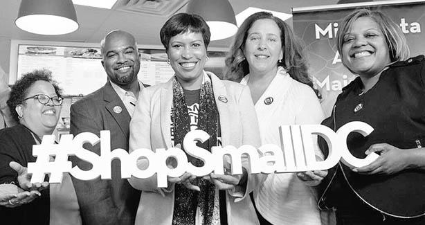 Mayor Bowser holding ShopSmallDC sign
